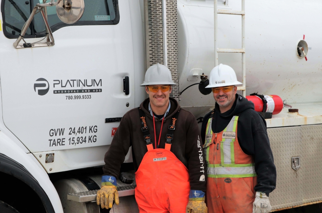 Two platinum employees smiling and standing in front of a platinum truck