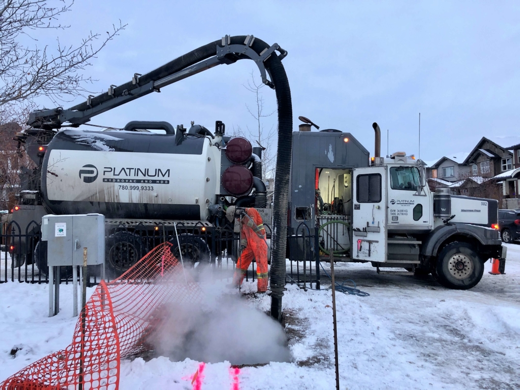A platinum employee using a platinum hydrovac truck to hydrovac a residential shallow utilities