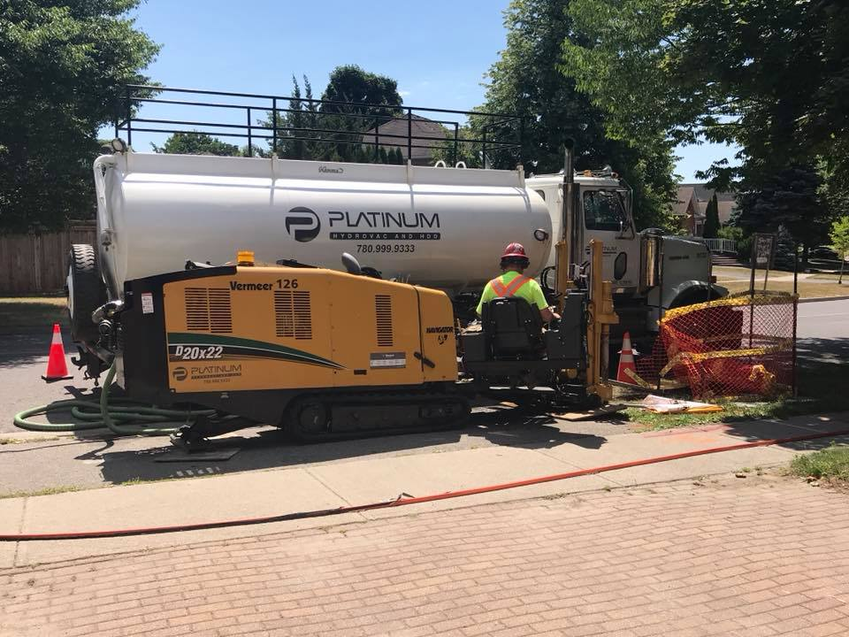 A platinum horizontal directional driller drilling into a residential street
