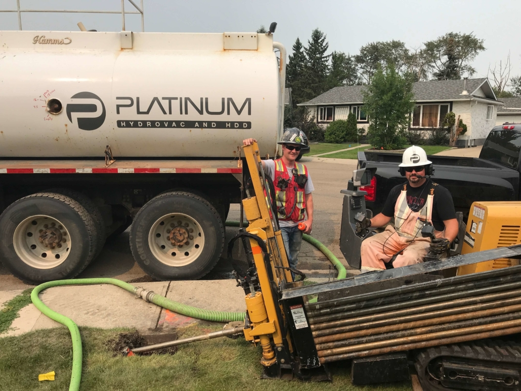 Two platinum team members, standing around the horizontal directional drill